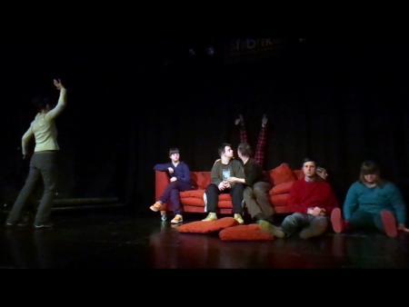 rotes Sofa auf einer  Bühne, drei DarstellerInnen sitzen auf dem Sofa, zwei davor, eine Darstellerin steht